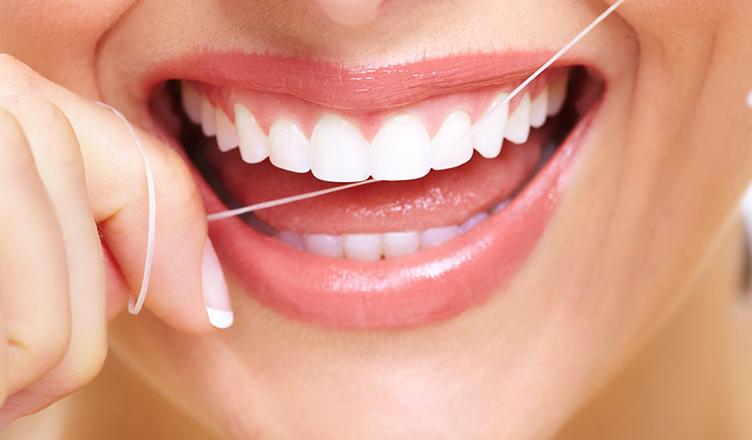 diş ipi kullanan kadın