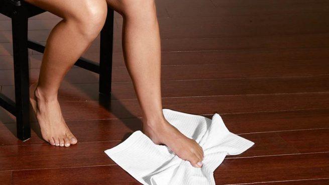 havluyu yerden ayağıyla almaya çalışan kadın