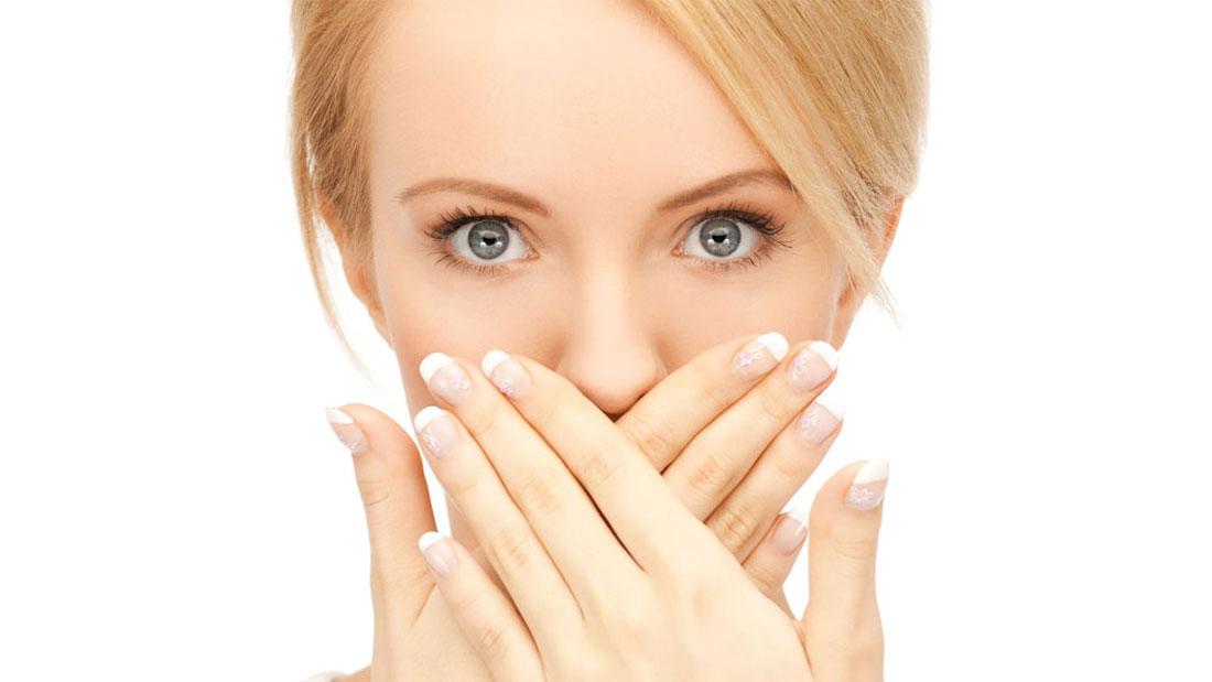 iki eliyle ağzını tutan kadın